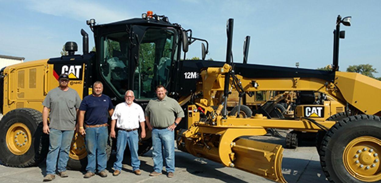 4 men standing in front of bulldozer smiling