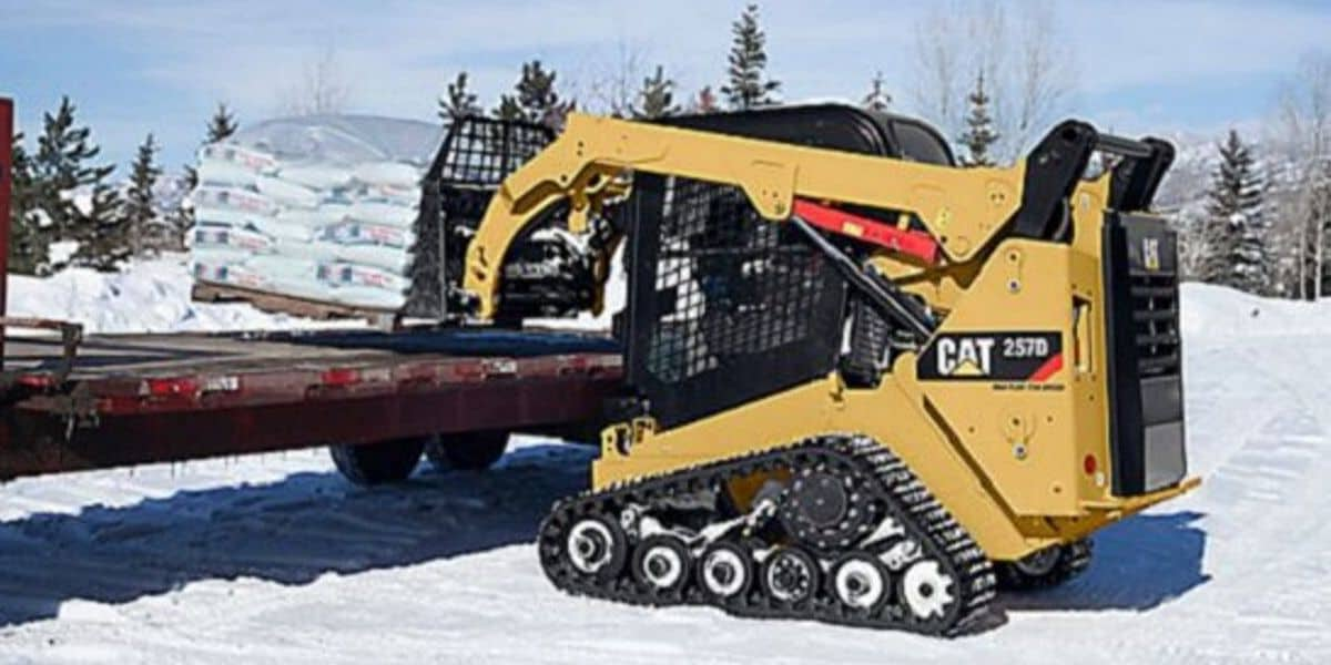 Track loader lifting salt onto truck in snowy field