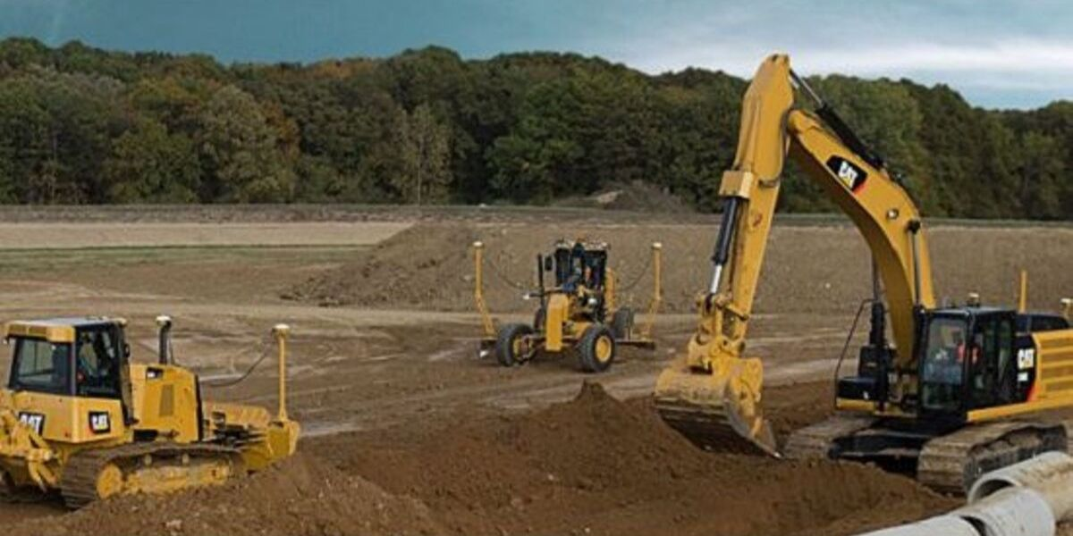 Three construction vehicles working in dirt field