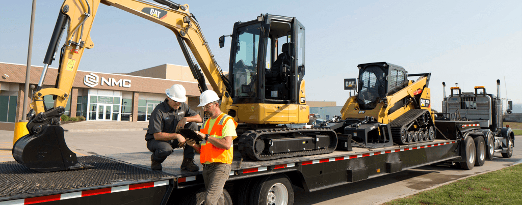 Two men talking in front of a truck carrying Cat heavy equipment