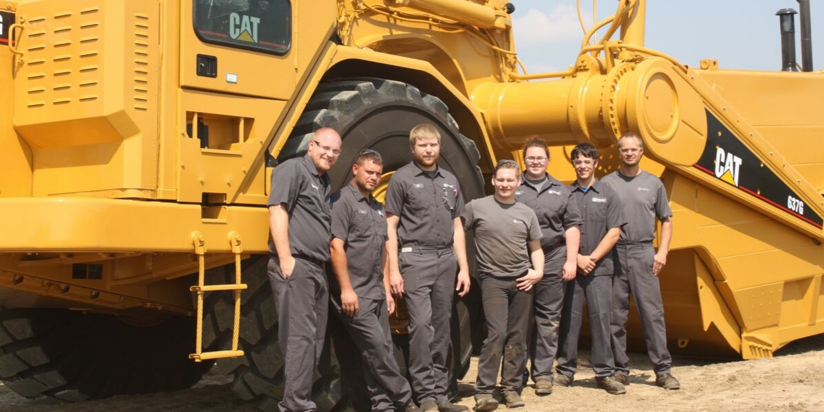 Group of NMC workers smiling in front of large vehicle