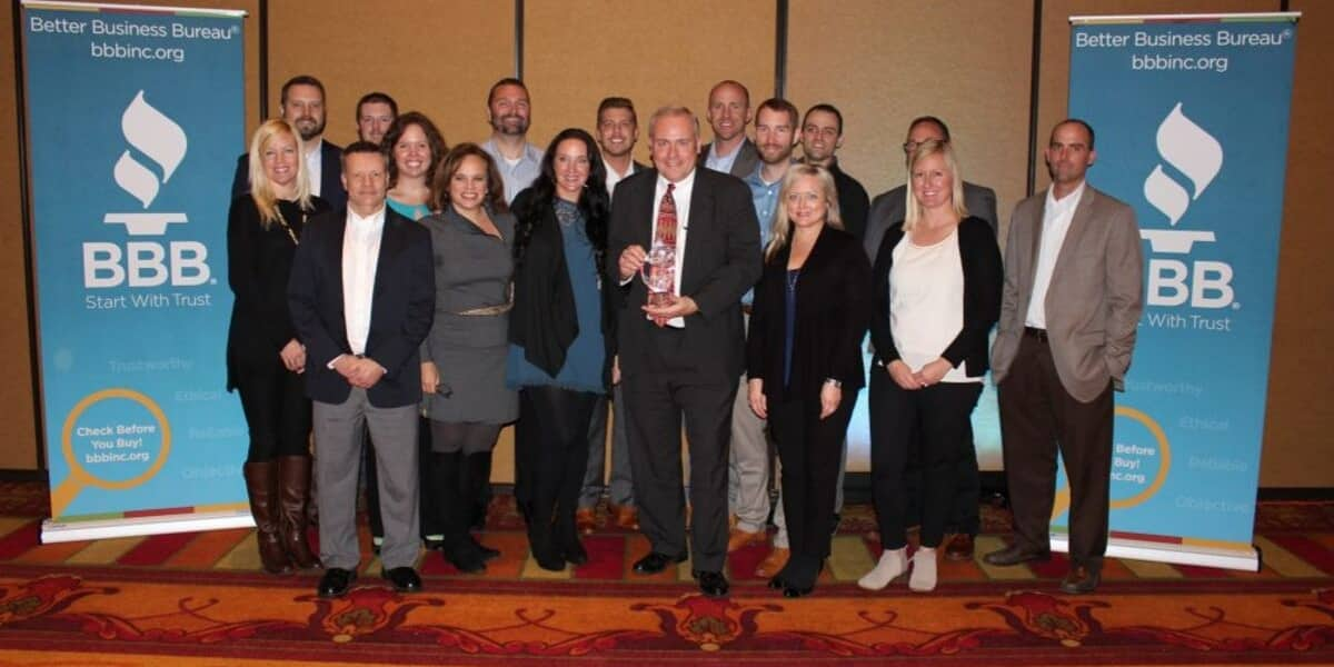 Group of NMC Cat employees at Better Business Bureau event with award