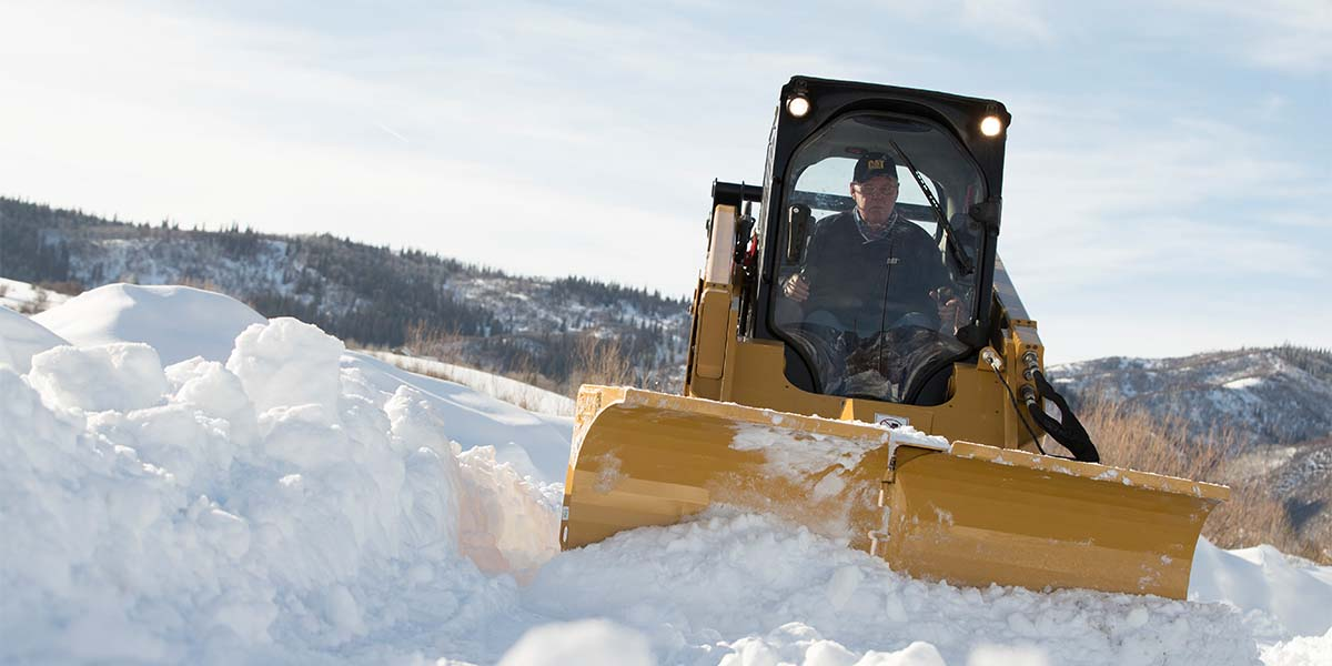 Older man driving Cat tractor in the snow