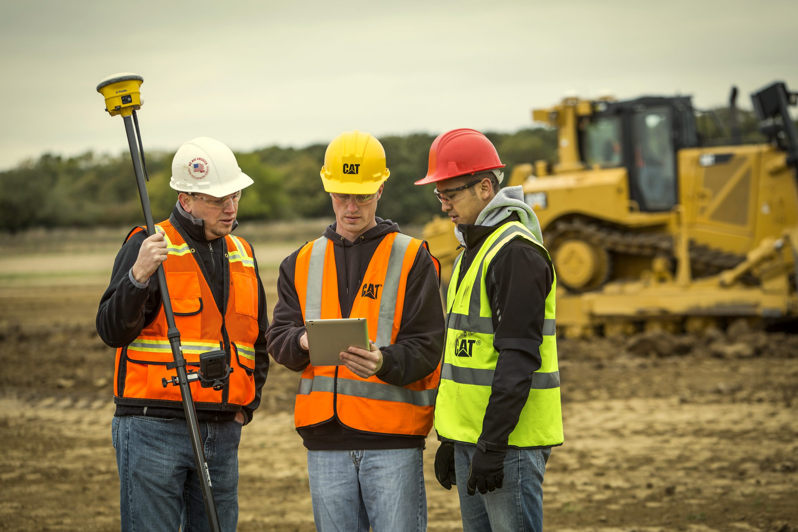3 construction workers talking in front of CAT construction equipment