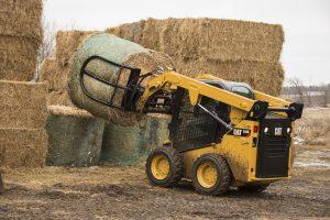 Cat skid steer loader moving large hay bales